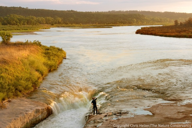 A photographer captures the late day light coming through the falls on the Niobrara River near the Norden Bridge.