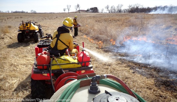 Burn crew member Aric Ping keeps the fire inside the mowed firebreak with a high-pressure spray of water.