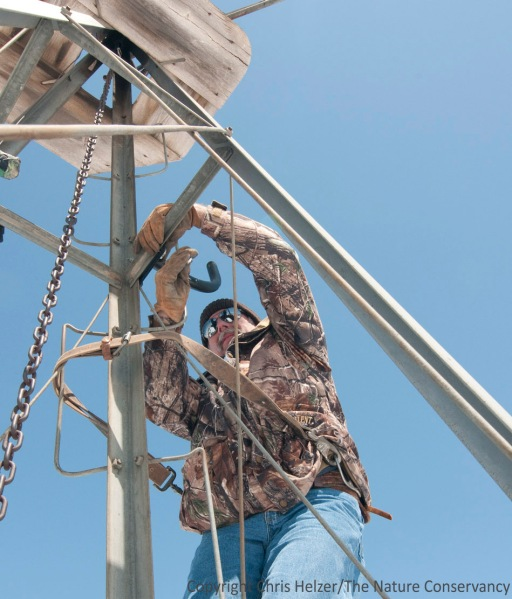 Jeff Dale fastens a camera mount near the top of a windmill tower.