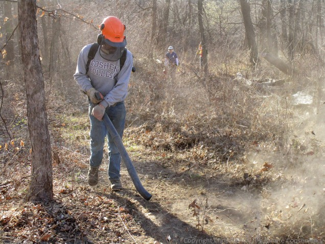 Firebreaks for the fire were mostly created by using a power leaf blower to clear out a narrow trail.  Nelson Winkel is shown here making a final pass around the breaks of the 100 acre burn unit.