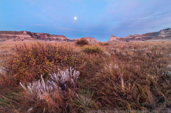 As the sun turned the sky pink to the east, the moon was dropping in the west.  Scotts Bluff National Monument.