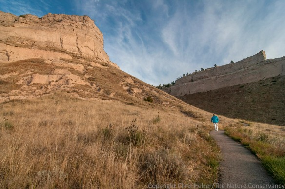 A hiker enjoys the paved trail and gorgeous weather at Scotts Bluff National Monument.