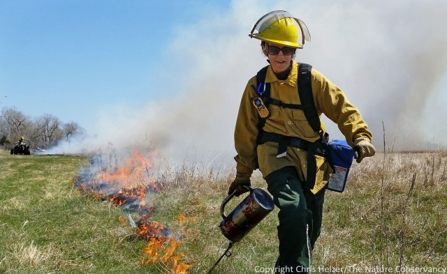 "Mardell Jasnowski lights a ""flanking head fire"" at a recent burn in our Platte River Prairies."