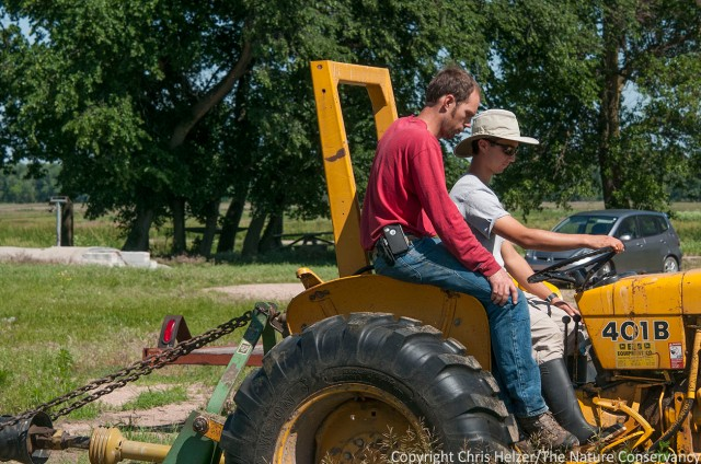 Nelson Winkel teaches Hubbard Fellow Evan Barrientos (in hat) how to drive a tractor.
